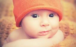 Gulligt nyfött behandla som ett barn i stuckit orange hattlock arkivbild