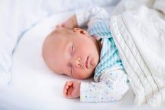 Gulligt nyfött behandla som ett barn i vit säng Arkivfoto