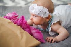 Gulligt nyfött behandla som ett barn lukta blommor Arkivfoto