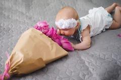 Gulligt nyfött behandla som ett barn lukta blommor Royaltyfri Foto