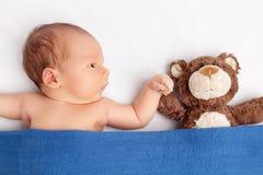 Gulligt nyfött behandla som ett barn med en nallebjörn under en filt Arkivfoton