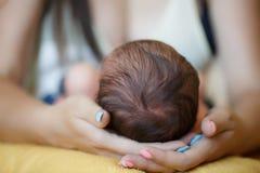 Gulligt nyfött behandla som ett barn sömnar i armarna av min moder Royaltyfri Fotografi