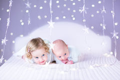 Gulligt nyfött behandla som ett barn och hans härliga litet barnsyster som spelar toget Royaltyfri Bild