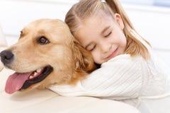 Gulligt omfamna för liten flicka och för hund arkivfoto