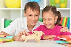 Gulligt pojke- och systersammanträde på tabellen och se modellen royaltyfri bild