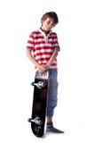 Gulligt pojkeanseende med skateboarden,  Royaltyfri Bild