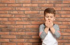 Gulligt pojkelidande från hosta nära tegelstenväggen arkivbilder