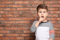 Gulligt pojkelidande från hosta nära tegelstenväggen fotografering för bildbyråer