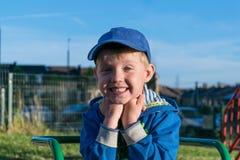 Gulligt pojkesammanträde på lekplatsen som rymmer händer nära hakan, leenden och gyckel Royaltyfri Bild