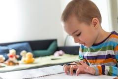 Gulligt pojkesammanträde på tabellen och spela med färgläggningboken Arkivfoton