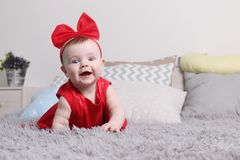 Gulligt roligt behandla som ett barn i röd klänning och bugar leenden Royaltyfri Fotografi