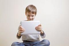 Gulligt skämtsamt lyckligt barn med den digitala minnestavladatoren som spelar lekar Fotografering för Bildbyråer
