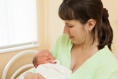Gulligt sova som är nyfött, behandla som ett barn barnet på moderhänder Arkivbild