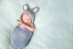 Gulligt sova som är nyfött, behandla som ett barn klätt som påskkanin Royaltyfri Foto