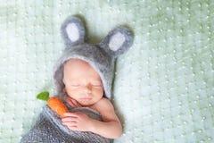 Gulligt sova som är nyfött, behandla som ett barn klätt som påskkanin Arkivfoton
