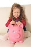 Gulligt spela för liten flicka sätter myntet i den enorma spargrisen på soffan Arkivfoton