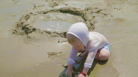 Gulligt spela för pys leker med sand på havsstranden BarnOS p? semester i sommar p? stranden p? semestrar stock video