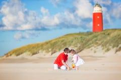 Gulligt syskon på stranden bredvid fyren Royaltyfria Bilder