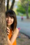 Gulligt thailändskt flickanederlag bak treen Royaltyfria Bilder