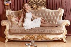Gulligt ung flickasammanträde på en soffa royaltyfri fotografi