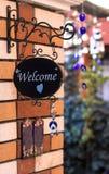 Gulligt välkommet tecken på tegelstenväggen royaltyfria bilder