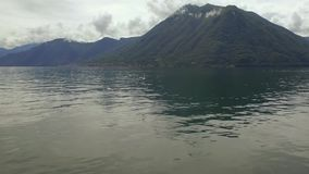 Gulls at lake with mountains and towns in Italy stock video footage
