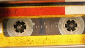 Gulna ljudkassetten i bandspelaren som spelar och, roterar stock video
