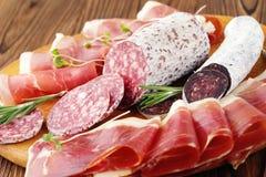 Guloseimas da carne do close-up, fatias finas de jamon e salsicha italiana em uma placa de madeira foto de stock