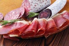 Guloseimas da carne do close-up, fatias finas de jamon e salsicha italiana em uma placa de madeira fotografia de stock royalty free