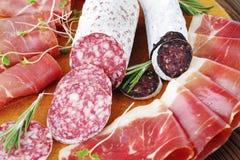 Guloseimas da carne do close-up, fatias finas de jamon e salsicha italiana em uma placa de madeira fotos de stock