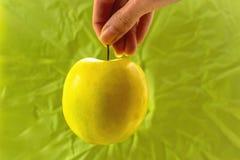 Gult äpple i hand på grön bakgrund royaltyfri fotografi