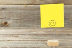 Gult anmärkningspapper på en hållare på grå träbakgrund Arkivfoton