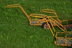 Gult bagage carts anseende i gräset Fotografering för Bildbyråer