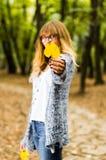 gult blad i handen av en härlig flicka royaltyfri bild