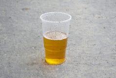 Gult drinköl i den plast- koppen på trottoaren royaltyfri foto