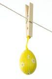 Gult easter ägg som hänger från en fodra Arkivbild