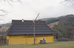 Gult hus och brunnen. Royaltyfri Fotografi