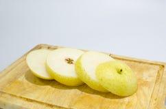 Gult kinesiskt päron för skiva på den wood skärbrädan Royaltyfri Fotografi