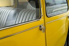 Gult klassiskt bildörrhandtag och fönster med de svarta bilsätena royaltyfria bilder