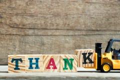 Gult kvarter K för bokstav för leksakgaffeltruckhåll som ska uttryckas för att tacka arkivfoton