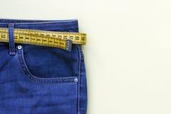 Gult måttband i jeans på bakgrund, begrepp av viktförlust, kopieringsutrymme royaltyfri bild