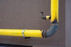Gult oavslutat gasrör på byggnadsväggen Begreppet av gasification av hus arkivbilder