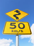 Gult och svart slingrigt vägmärke 50km/h Arkivbild