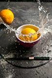 Gult orange falla in i en kopp av vatten Fotografering för Bildbyråer