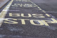 Gult ord för vägsignalhållplats som är skriftligt på asfalt fotografering för bildbyråer