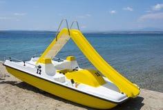 Gult pedal- fartyg på en strand Royaltyfri Foto