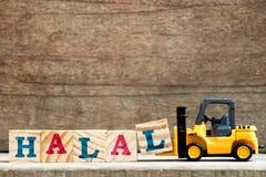 Gult plast- kvarter L för bokstav för leksakgaffeltruckhåll som uttrycker halal Arkivbilder