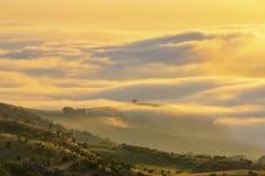 Gult solljus på låga moln i dalen royaltyfria foton
