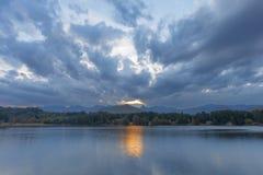 Gult solsken till och med molnen reflekterar på vattnet arkivbild
