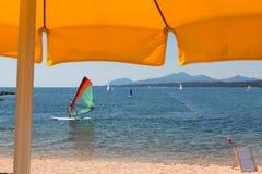 Gult strandparaply, surfare, kullar och hav i bakgrund Arkivbild
